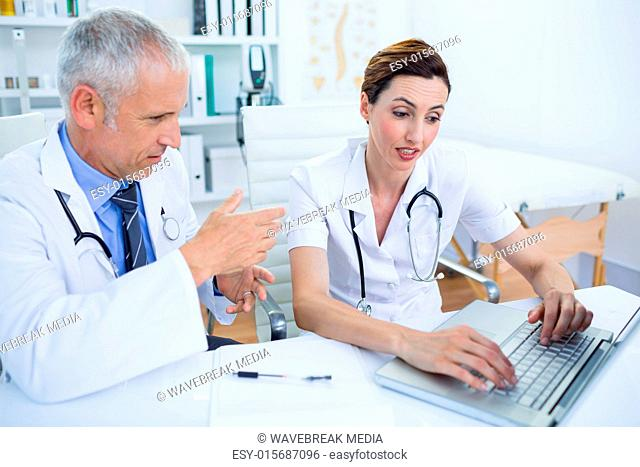 Concentrated medical colleagues discussing and working with laptop