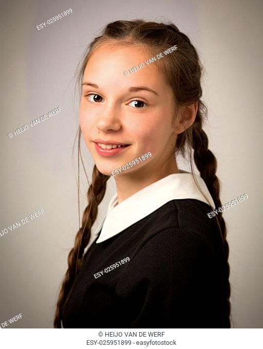 Studio portrait of a beautiful teenage girl with extremely long hair plaits wearing a black dress with a white collar isolated against a grey background