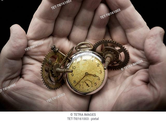 Hands holding antique clock and gears
