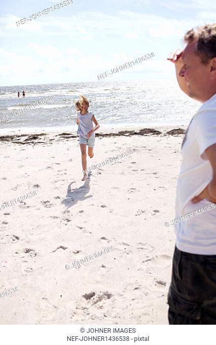 Girl running to her father on beach