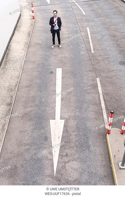 Businessman standing on road with arrow sign