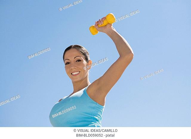 Hispanic woman exercising with dumbbell