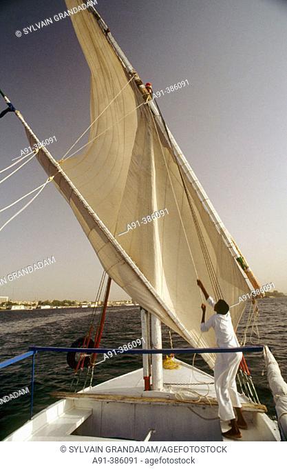 Hoisting a felucca sail on Nile river, Aswan. Nubia, Egypt