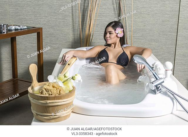 Young beautiful woman with flower in hair lying in hot bath in massage center enjoying health procedure