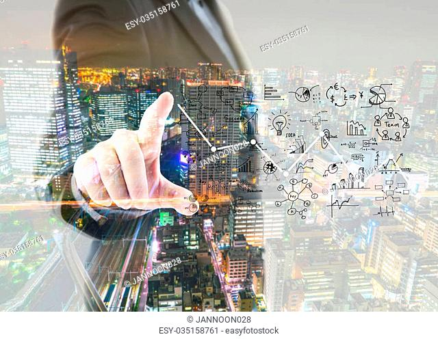 Double exposure of business man touching an imaginary screen with cityscape