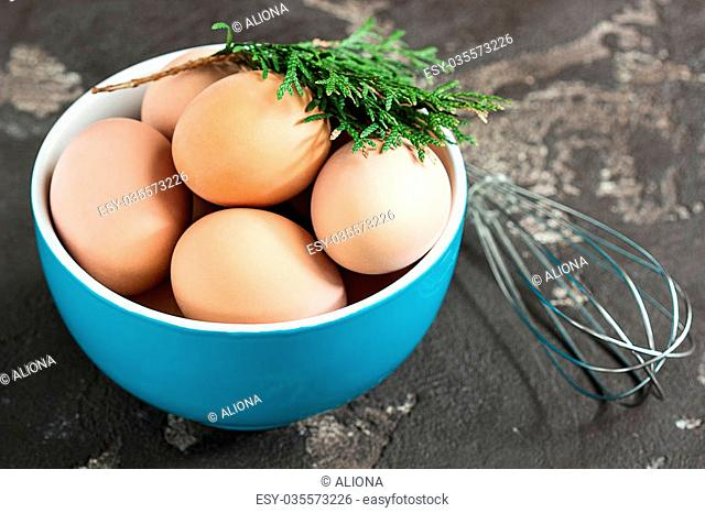 Fresh chicken eggs in a bowl with a whisk on a concrete background