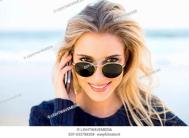 Cheerful gorgeous blonde on the phone looking over her sunglasses on a beautiful wild beach