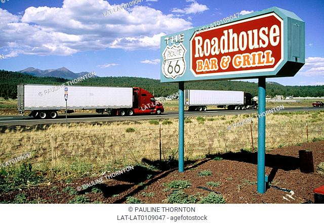 A sign to Route 66 diner on an old national highway route with trucks behind. Route 66 is nearly 2,500 miles long ans runs from Chicago,Illinois to Santa Monia