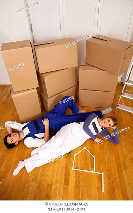 young couple new home house moving in boxes tired
