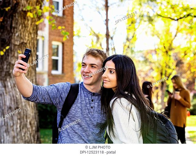 A couple who are university students posing for a self-portrait with a smart phone with a small group of friends in the background; Edmonton, Alberta, Canada