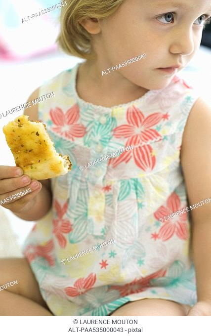 Little girl eating bread, looking away