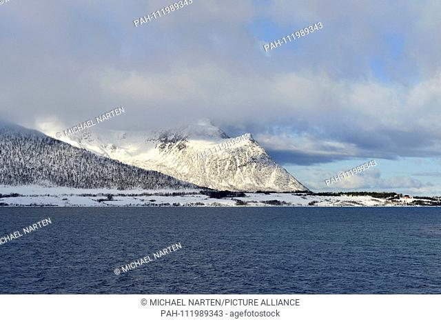The Risøysound and the Vesterålen Island Andoya with snow-white mountains surrounded by clouds, 10 March 2017 | usage worldwide