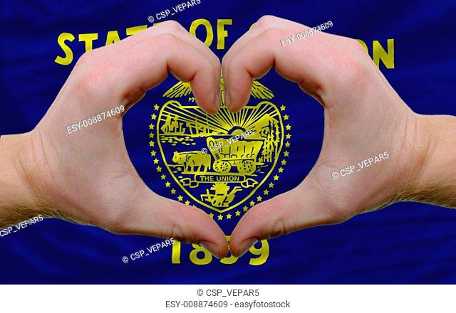 Gesture made by hands showing symbol of heart and love over us state flag of oregon