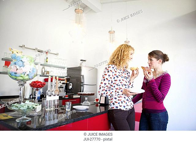 Two women in a kitchen eating and talking