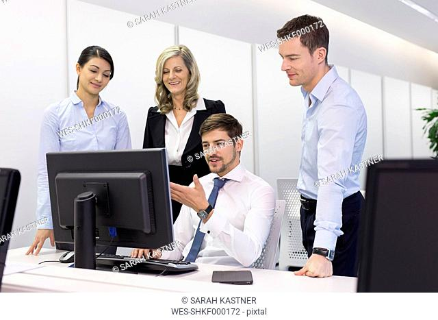 Businesspeople talking at desk in office