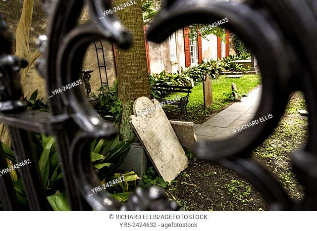 A tombstone rests on a palm tree in the garden of the French Huguenot Church along Queen Street in historic Charleston, SC