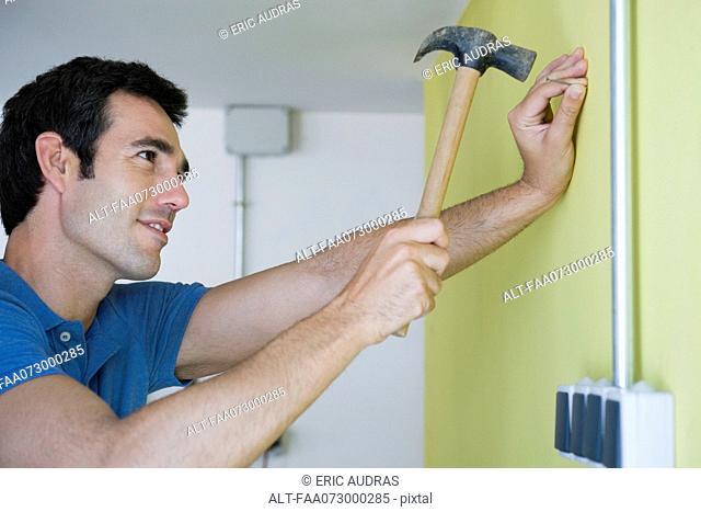 Man hammering nail into wall