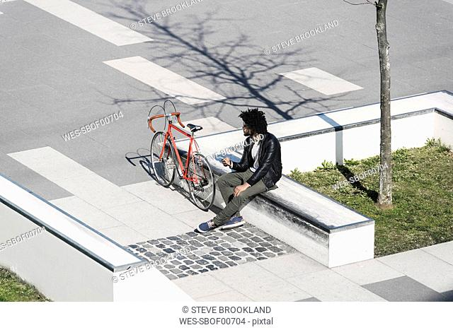 Man sitting in city skatepark holding his smartphone next to his bicycle