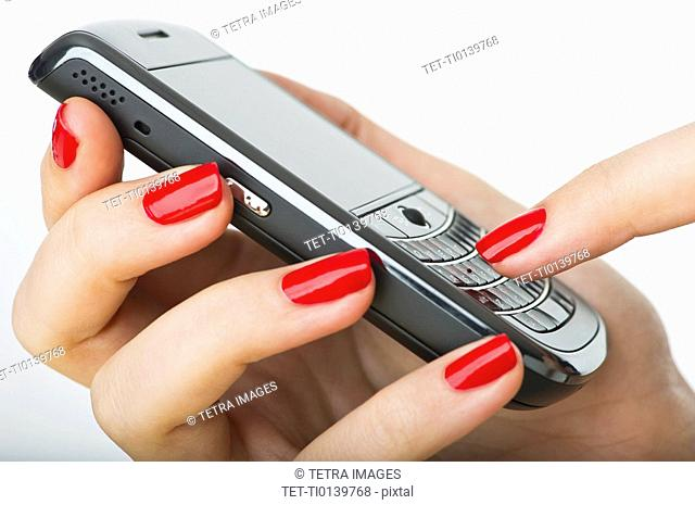 Woman wearing red nail polish texting on cell phone