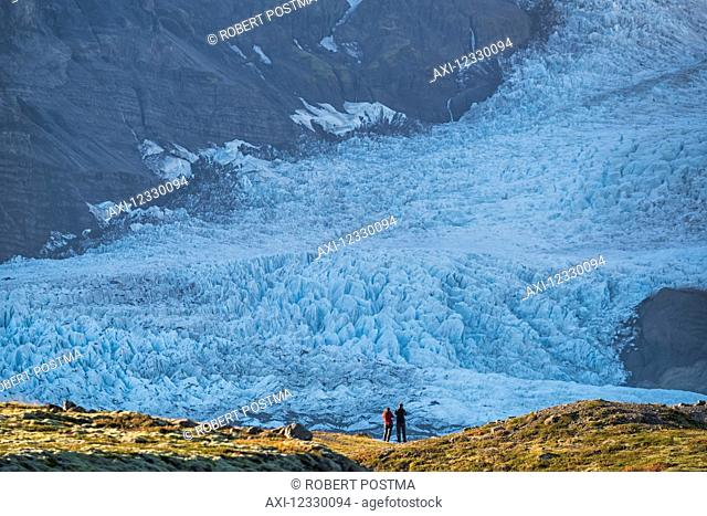 A Couple Standing In Front Of A Glacier Along The South Coast Of Iceland, Admiring Nature At Its Best; Iceland