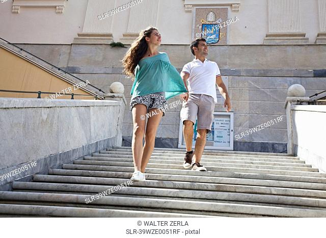 Couple climbing steps of ornate building