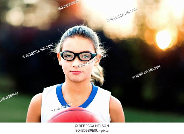 Portrait of girl wearing sports goggles holding basketball