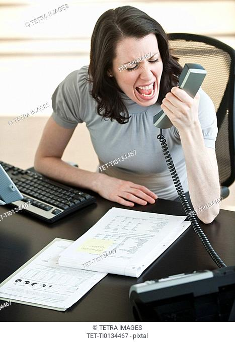Stressed business woman using telephone in office