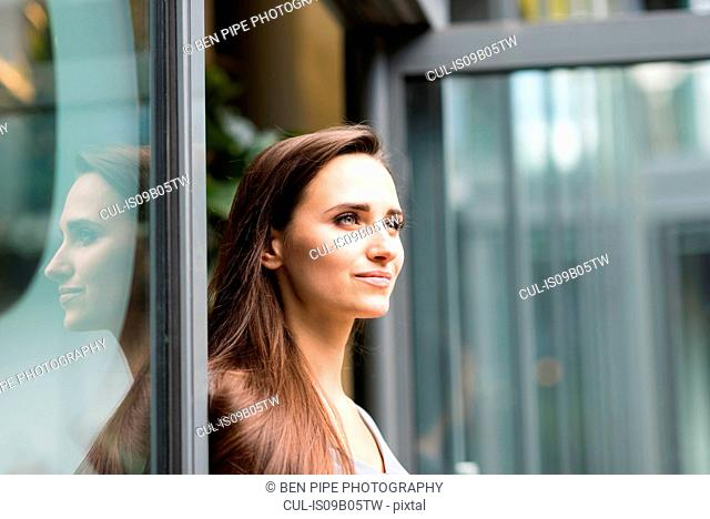 Young businesswoman leaning against office doorway, London, UK