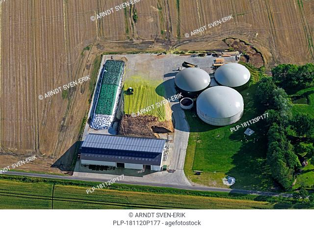 Aerial view over anaerobic digestion plant showing digesters with inflatable biogas holders, Schleswig-Holstein, Germany