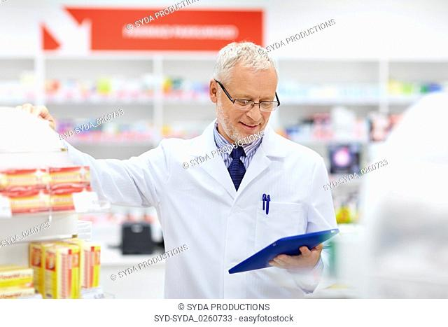 senior with tablet pc at pharmacy
