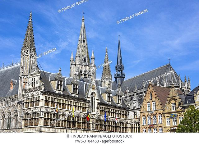 Detail of traditional Flemish architecture in the restored Cloth Hall, Grote markt, Ypres, Belgium with the spire of St Martens Kathedraal behind
