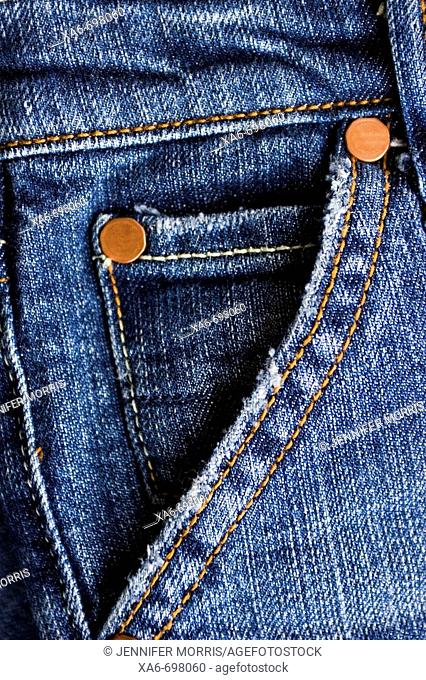 A close-up shot of the pocket of a pair of blue jeans, featuring the stitching and copper rivets