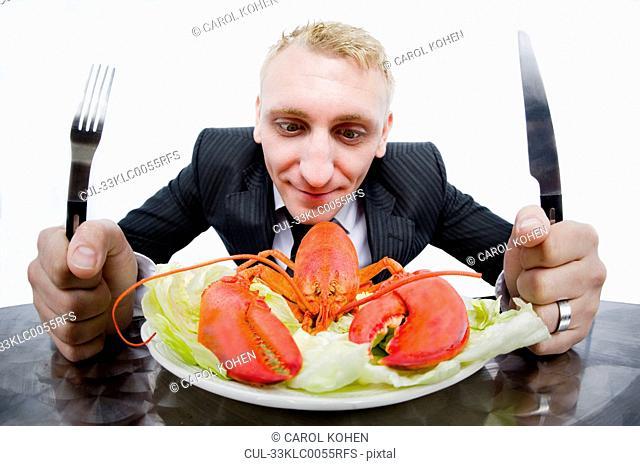 Businessman eating plate of lobster