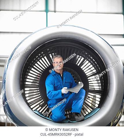 Worker sitting in airplane engine