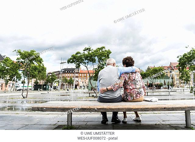 Germany, Mannheim, back view of senior couple sitting on a bench hugging each other