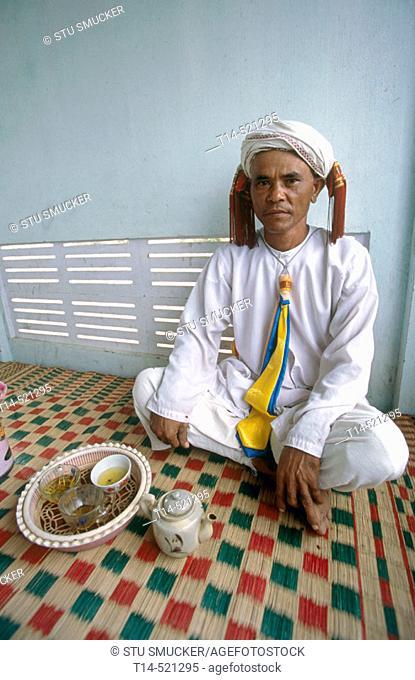 An ethnic Cham man named Ong Quan enjoys a cup of tea on his patio in Tuan Tu village. Ninh Thuan province. Vietnam