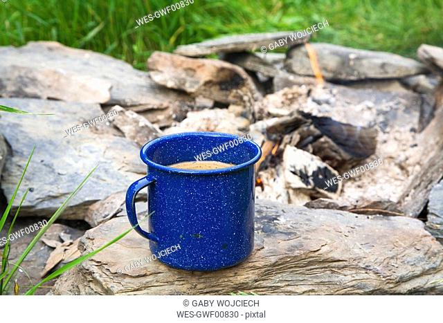 Coffee mug at campfire, close up