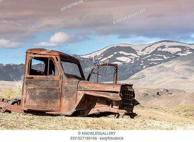 Old rusted truck and Idaho mountains with snow on them