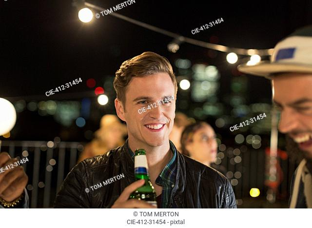 Smiling young man drinking beer at rooftop party