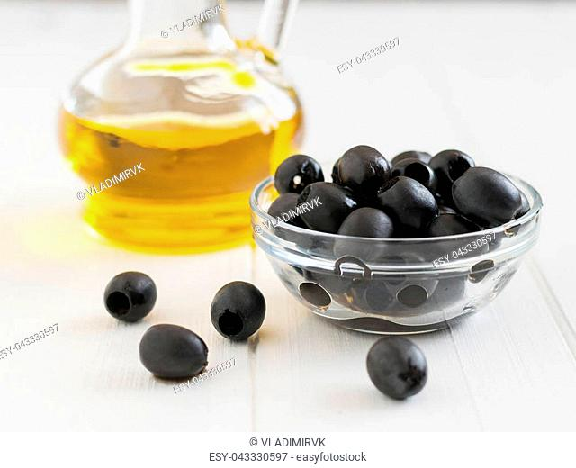Cup with scattered olives and a bottle of olive oil on a white table. Fresh olives in a glass bowl