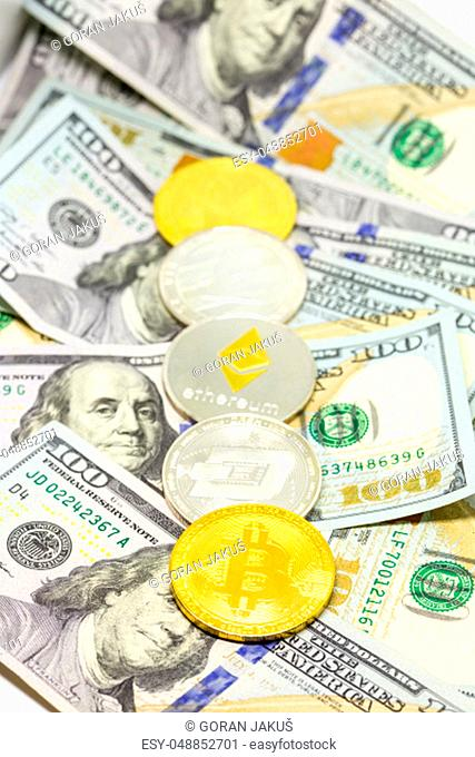Lined up cryptocurrency coins displayed on a heap of one hundred dollar bills with focus on bitcon coin