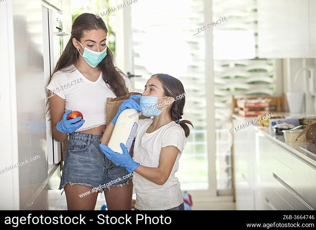 daughter and mom at home wearing masks and gloves because of the pandemia