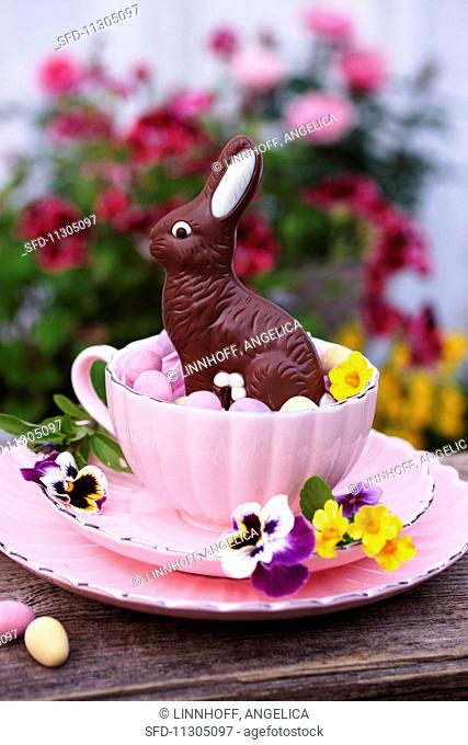 A place setting decorated with a chocolate Easter bunny, flowers and sugared eggs