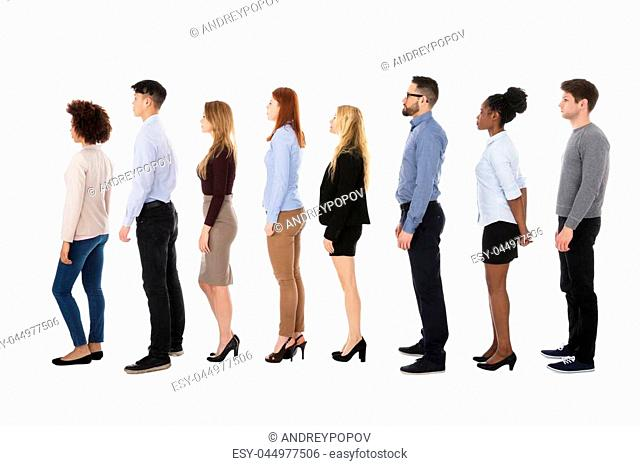 Group Of College Students Standing In Row Against White Background