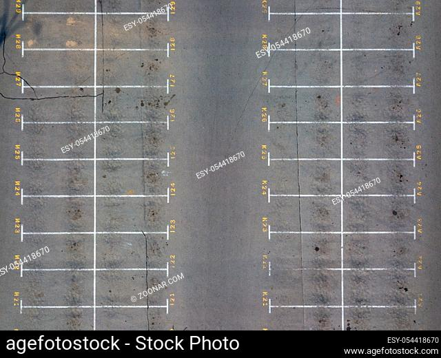 Panoramic view from drone above empty parking with white marking lines on asphalt with numbered places. Parking cars background