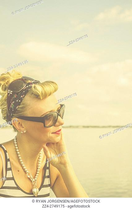 Pensive and dreaming pin up woman with retro 50s hairstyle and headband wearing two pairs of sunglasses and bead necklace against sea background