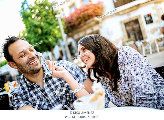 Couple having fun while eating an ice cream in a street cafe