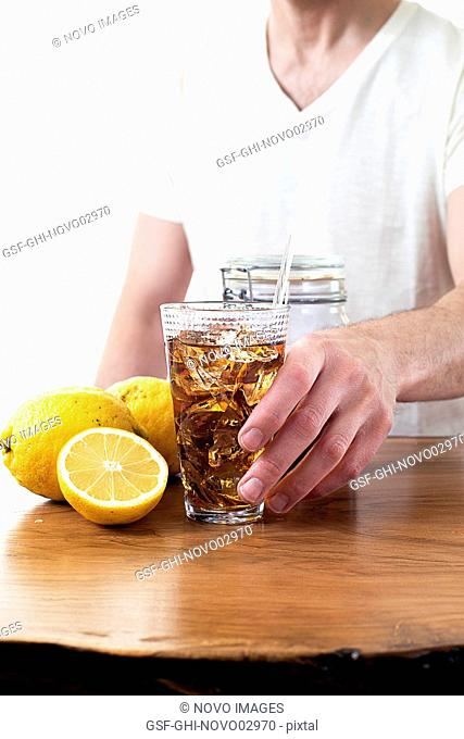 Man Grabbing Glass of Iced Tea from Wood Table