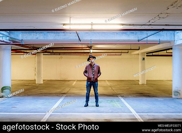 Man with hands in pockets standing in parking lot