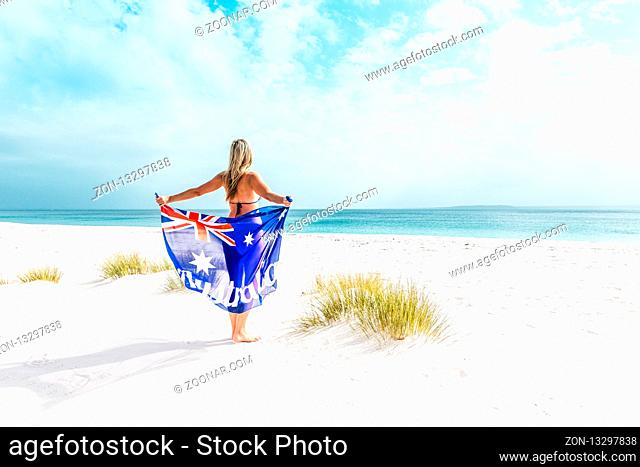 Suntanned woman on a beautiful idyllic beach in Australia. She is holding a loosely draped Australian flag
